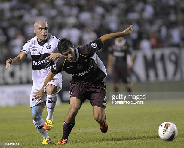 Lanus' Carlos Araujo vies for the ball with Olimpia's Vladimir Marin during their Copa Libertadores football match in Asuncion Paraguay on February...