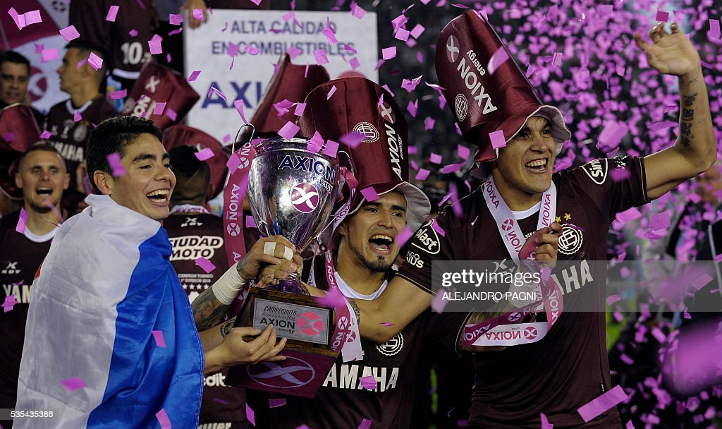 Lanus' footballers celebrate after winning the Argentina First Divison football tournament at the Momnumental stadium in Buenos Aires, Argentina, on May 29, 2016. Lanus won 4-0 to San Lorenzo and became champion. / AFP / ALEJANDRO
