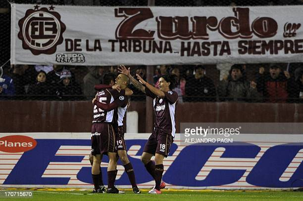 Lanus' midfielder Guido Pizarro celebrates with teammates after scoring their team's second goal against River Plate during their Argentine First...