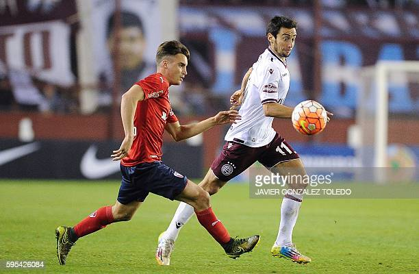 Lanus's forward Ciro Rius and Argentina's Independiente defender Nicolas Tagliafico run for the ball during their Sudamericana Cup football match at...
