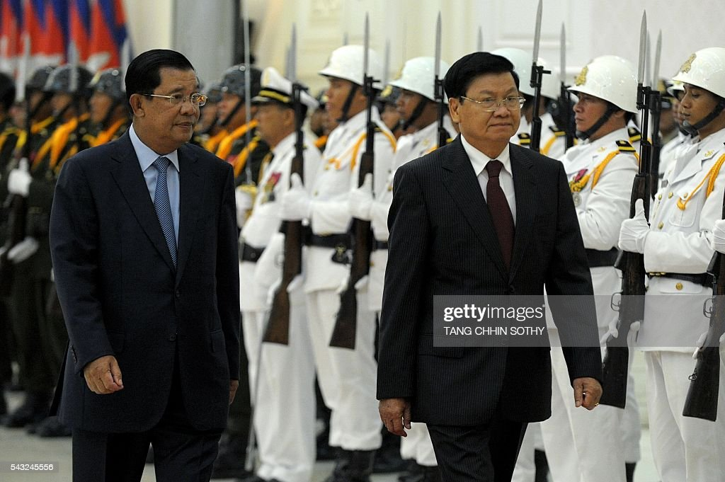Lao Prime Minister Thongloun Sisoulith (R) and Cambodian Prime Minister Hun Sen (L) walk past an honour guard upon his arrival at the Peace Palace in Phnom Penh on June 27, 2016. Thongloun Sisoulith is on a two-day visit to Cambodia. / AFP / TANG