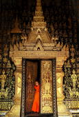 Laos Buddhist monk stands in front of temple at Wat Xieng Thong during the Songkran festival on April 13 in Luang Prabang Laos The Songkran Festival...