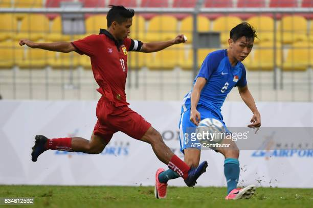Laos defender Sipasong Bounthavy vies for the ball with Singapore's Joshua Bernard Pereira during their men's football preliminary match at the 29th...