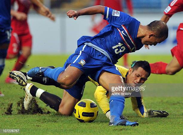 Laos goal keeper Sengphachan challenges Thailand's Therdsak Chaiman vie during the qualification match of the AFF Suzuki Cup 2010 in Jakarta on...