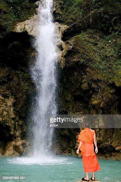 Laos, Luang Prabang, Buddhist monk facing falls, rear view