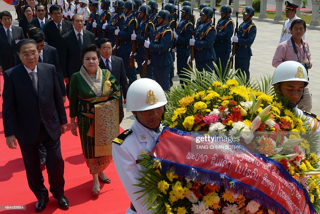 Laos President <a gi-track='captionPersonalityLinkClicked' href=/galleries/search?phrase=Choummaly+Sayasone&family=editorial&specificpeople=556173 ng-click='$event.stopPropagation()'>Choummaly Sayasone</a> (L) and his wife Keosaychay Sayasone (2nd R) walk past an honour guard (back R) as the pay their respects to a statue of late former king Norodom Sihanouk during their visit in Phnom Penh on February 26, 2015. Choummaly arrived here for a two-day official visit.