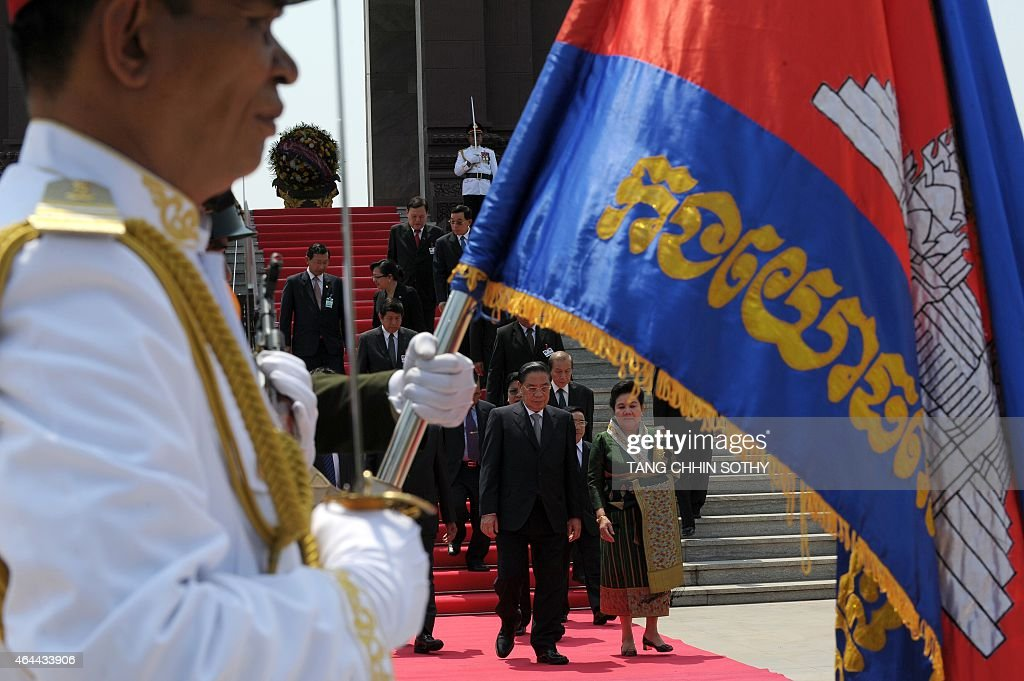 Laos President <a gi-track='captionPersonalityLinkClicked' href=/galleries/search?phrase=Choummaly+Sayasone&family=editorial&specificpeople=556173 ng-click='$event.stopPropagation()'>Choummaly Sayasone</a> (center L) as his wife Keosaychay Sayasone (center R) walk past an honour guard during a visit to the Independence Monument in Phnom Penh on February 26, 2015. Choummaly arrived here for a two-day official visit.