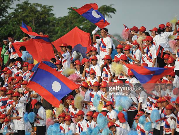 Laos supporters wave their national flag as their team take on Thailand in a women's football match during the 25th South East Asian Games in...