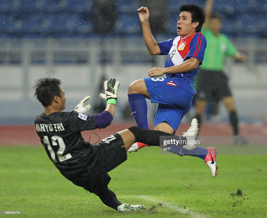 Laos's player Keoviengpheth Lithideth (R) fights for the ball with Indonesia's goalkeeper Wahyu Tri Nugroho during their AFF Suzuki Cup group B football match in Bukit Jalil Stadium outside Kuala Lumpur on November 25, 2012.