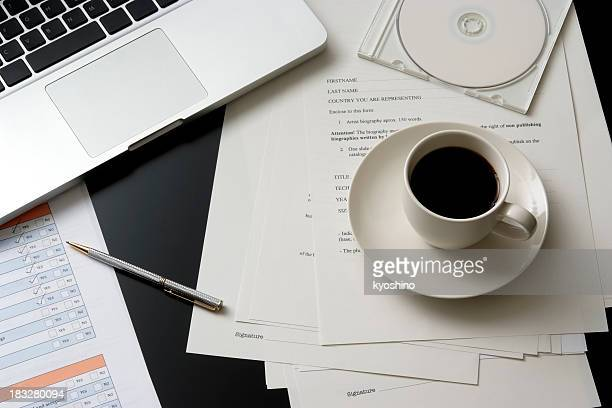 Laptop and a cup of coffee on messy office desk