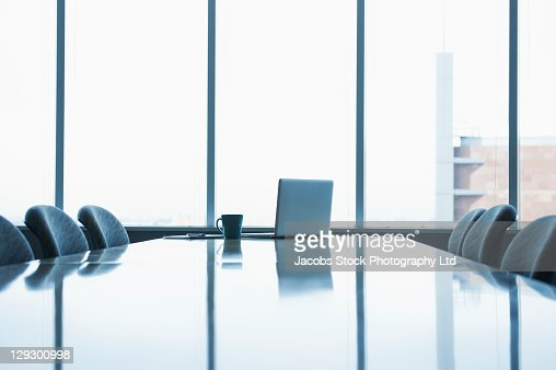 Laptop and coffee cup on conference room table : Stock Photo