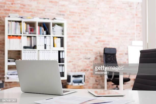 Laptop and digital tablet on desk in office
