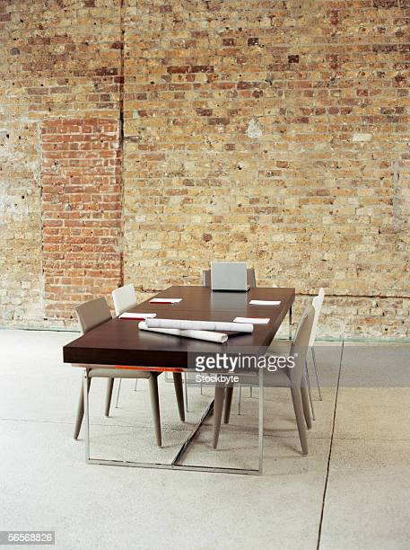 laptop and note pads with blueprints on a conference table