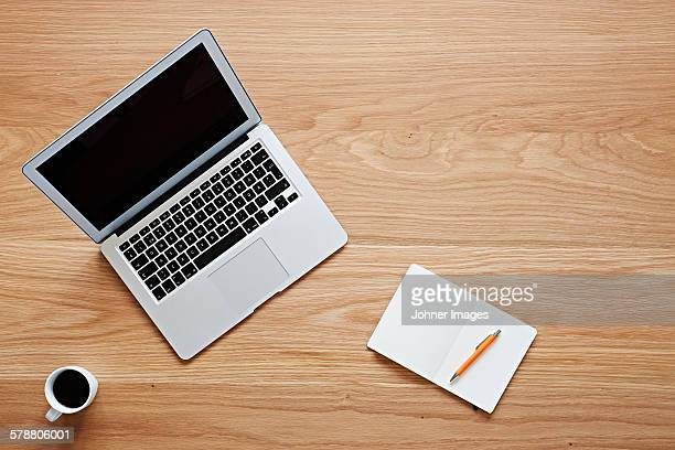 Laptop and notebook on wooden desk