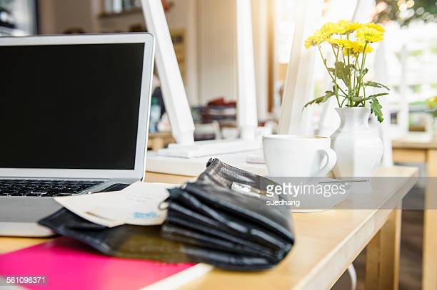 Laptop and open purse on table