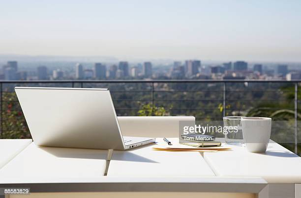 Laptop and paperwork on balcony table