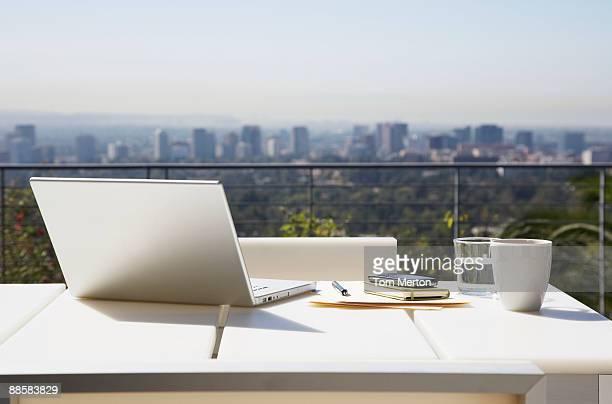 Ordinateur portable et documents sur la table balcon