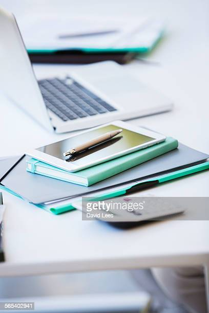 Laptop and paperwork on desk in office