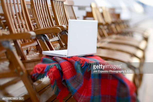 Laptop and rug on row of deckchairs