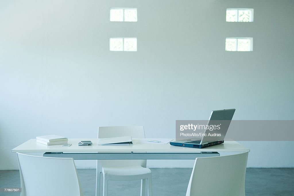 Laptop computer and cell phone on desk in office : Stock Photo