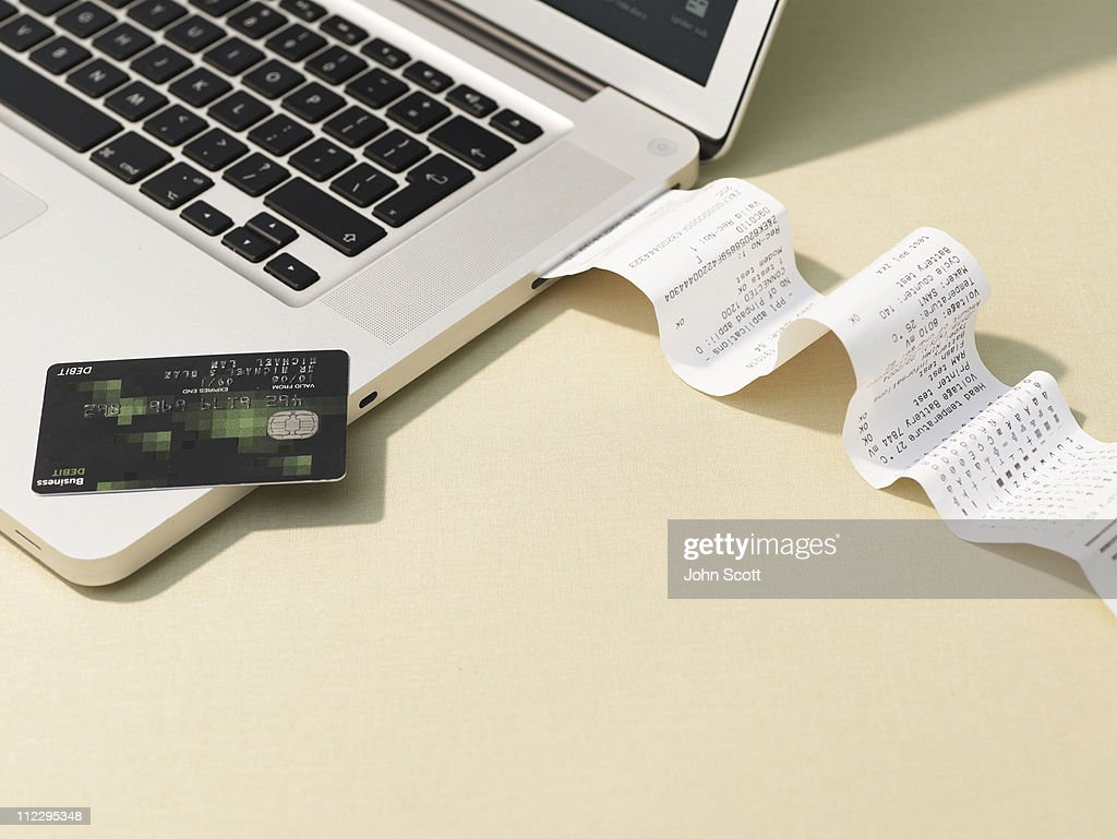 Laptop computer and reciept roll : Stock Photo