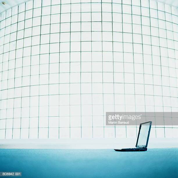 Laptop computer on floor by glass wall