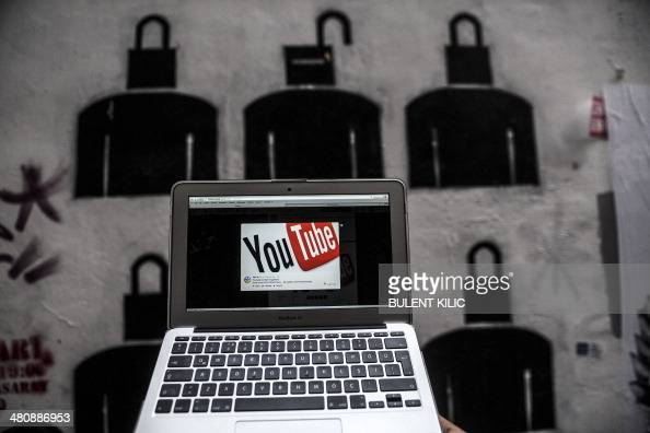 A laptop computer showing Youtube's logo on its screen is held in front of graffiti on March 27 2014 in Istanbul Turkey on March 27 banned...