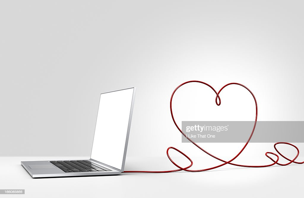 Laptop computer with cable forming a heart : Stock Photo