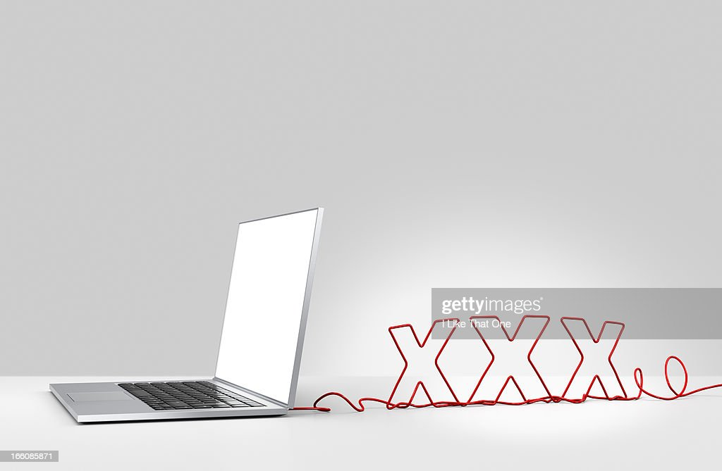 Laptop computer with cable forming 'XXX' : Stock Photo