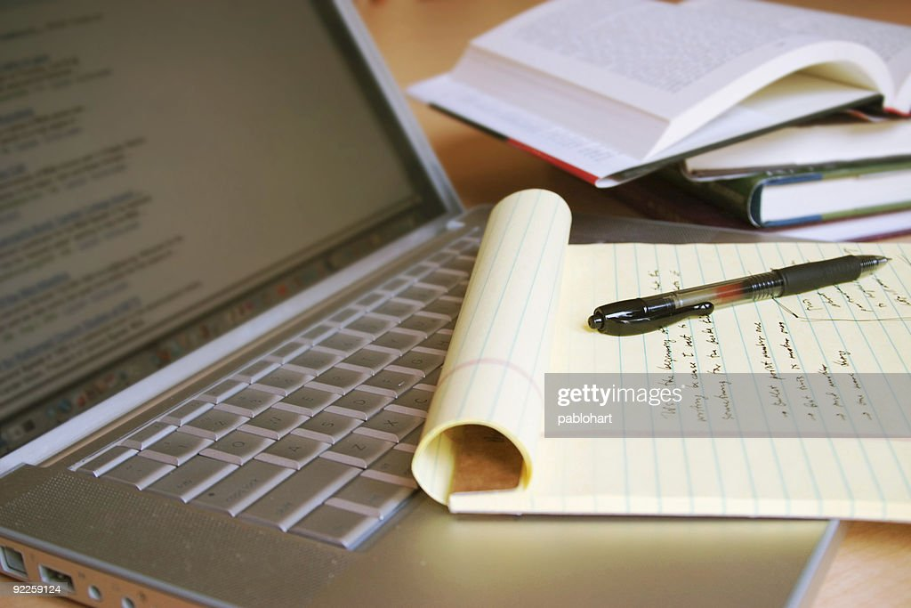 Laptop computer with yellow legal pad, pen and books