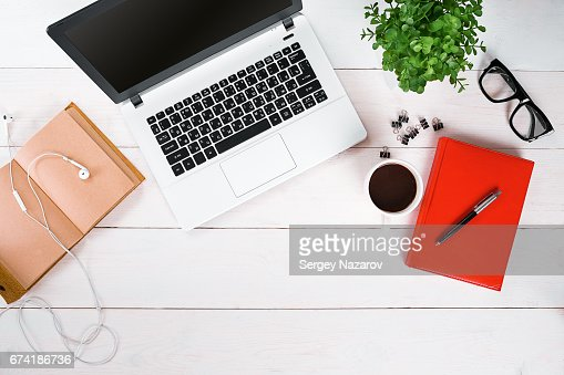 Laptop, digital tablet, diary, coffee cup and potted plant on work desk : Stock Photo
