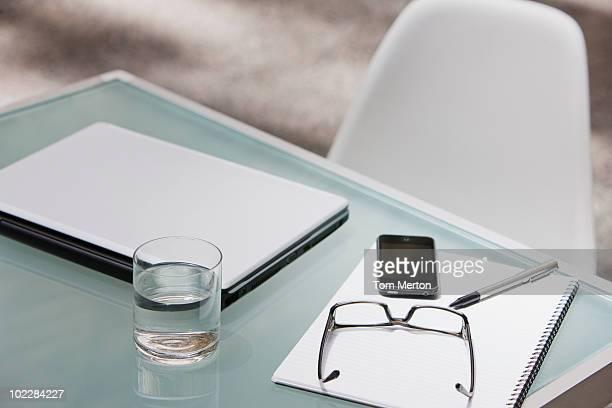 eyeglasses, Laptop, Handy und Notizblock auf Tisch