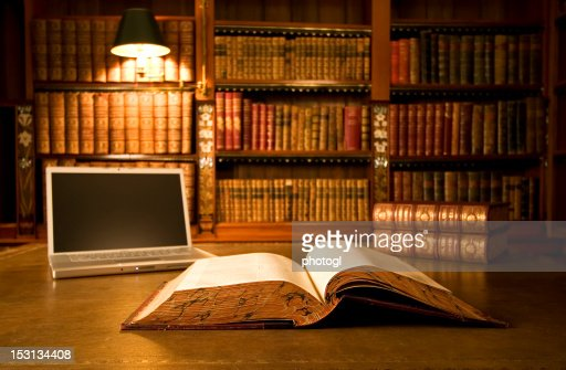 Laptop in classic library : Stock Photo