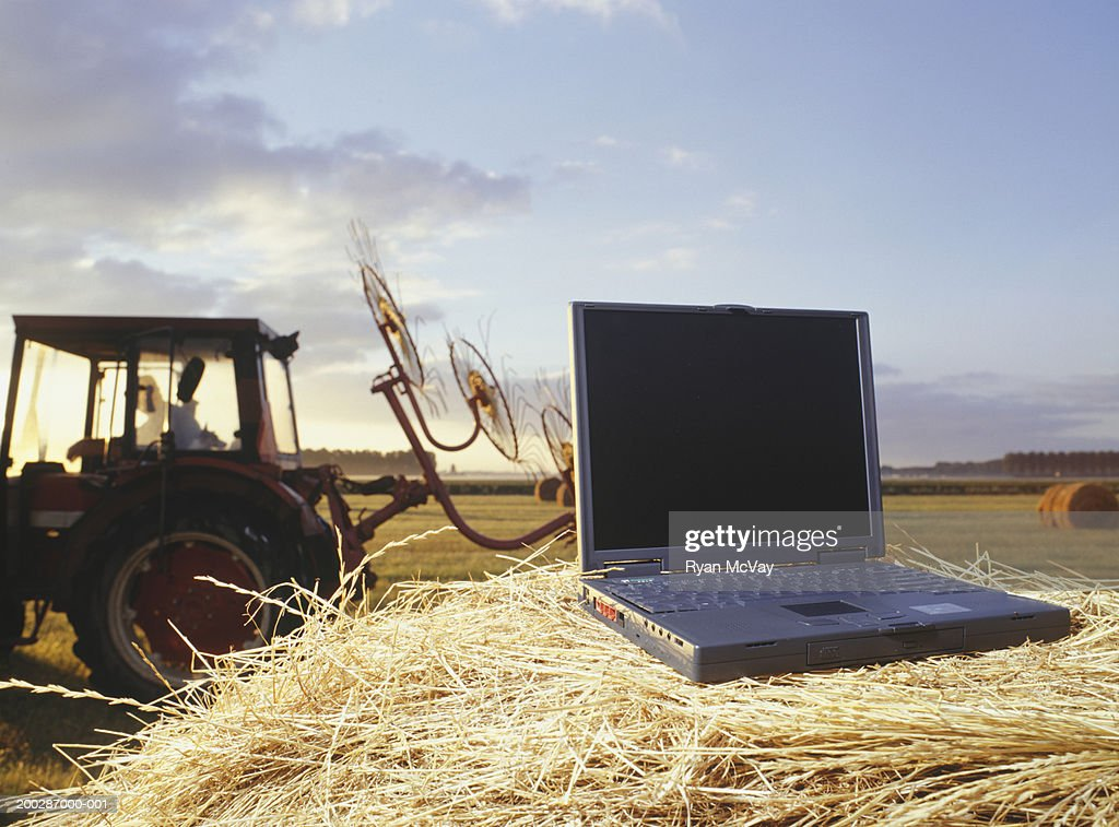 Laptop lying on hay bale, tractor driving past