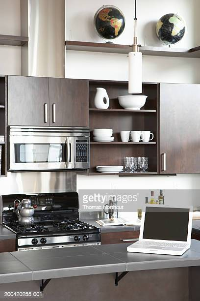 Laptop on counter in domestic kitchen