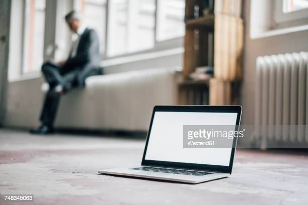 Laptop on floor with businessman in background