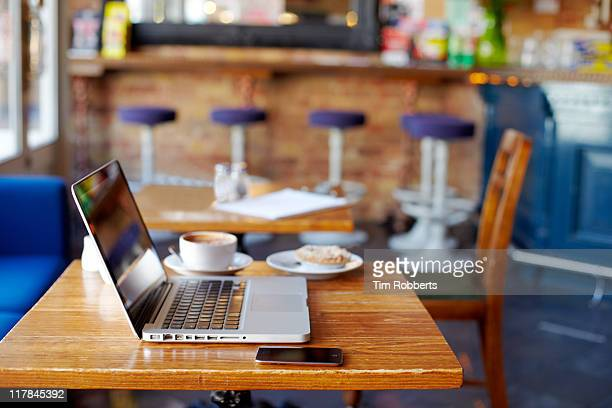 Laptop on table in coffee shop.