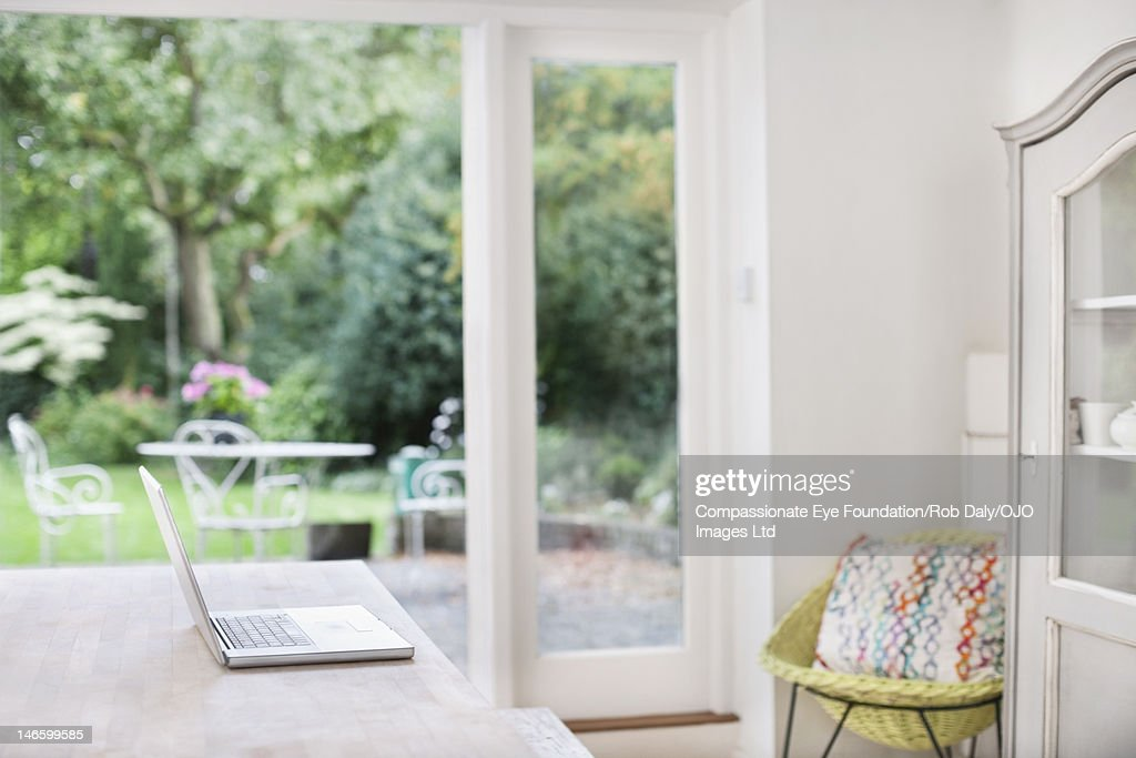 Laptop on table in kitchen : Stock Photo