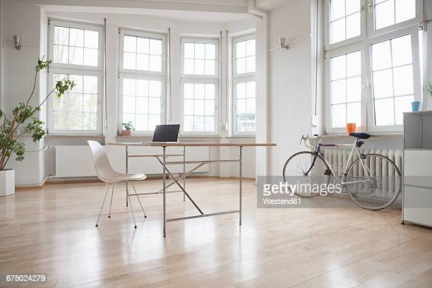 Laptop on table in sparse office