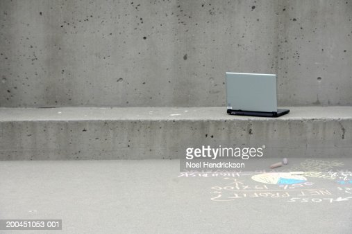Laptop outside building with writing on sidewalk : Stock Photo