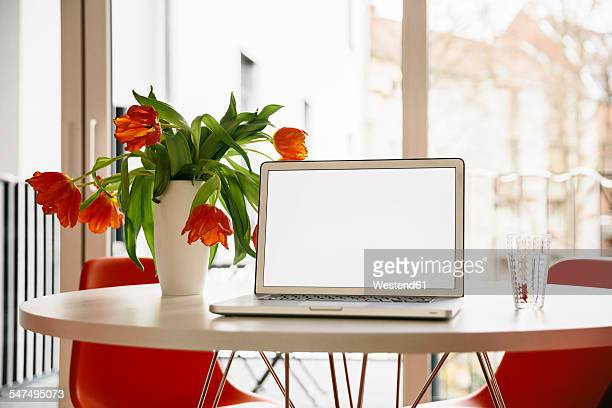 Laptop screen on a white round table with red tulips and chairs