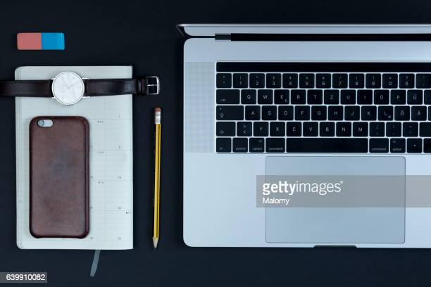 Laptop, smart phone, diary, pencil on black background, high angle view, flat lay, knolling, overhead, top view