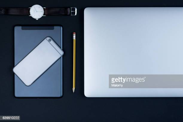 Laptop, smart phone, watch, pencil on black background, high angle view, flat lay, knolling, overhead, top view
