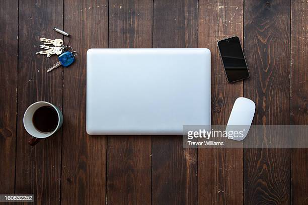 A laptop, smartphone, mouse, coffee, keys