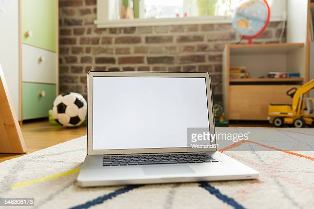 Laptop standing on carpet in childrens room