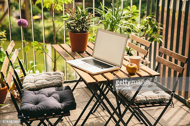 Laptop standing on table of balcony