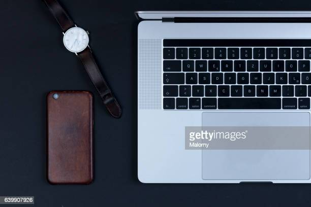 Laptop, watch, smart phone on black background, high angle view, flat lay, knolling, overhead, top view