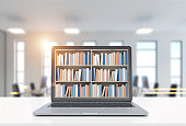 Laptop with bookshelves on its screen is standing on a white desk. A blurred office background. 3d rendering mock up toned image