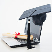 Laptop with diploma and mortar board