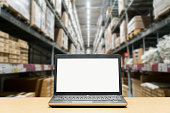 Laptop with white blank screen on brown wooden desk and blurred warehouse store background